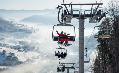 Young couple snowboarders riding up at ski lift at skiing and snowboarding winter resort in the mountains copyspace lifestyle vacation travelling sport extreme concept, Bukovel, Ukraine