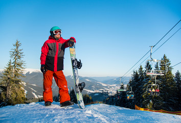 Full length portrait of a snowboarder wearing helmet skiing mask and colorful winter snowboarding clothing standing with his snowboard looking away in the evening copyspace active lifestyle sports