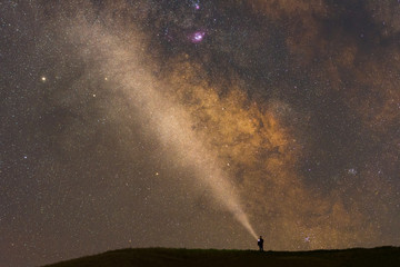 Person with flashlight pointing to the Milky Way