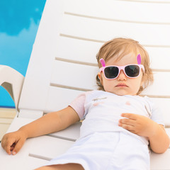 Endless summer Cute baby relaxing at sunbed near pool, resort.