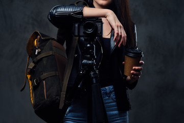 Brunette female photographer holds professional camera on a tripod.
