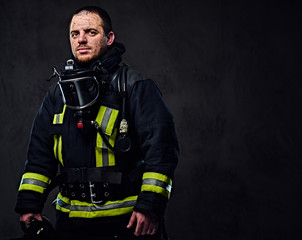 Studio portrait of a male dressed in a firefighter uniform.