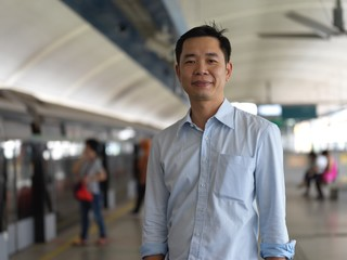 Asian chinese man smiling and waiting at for train transport