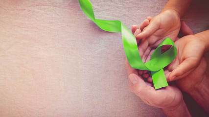 Adult and child hands holding Lime Green Ribbon, panoramic banner background, Mental health awareness and Lymphoma Awareness