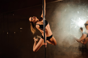Fototapeta young hot woman in sexy lingerie performs sensual pole dance. Go-go dancer obraz