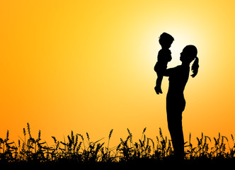 Silhouettes mother carries her son on sunset background