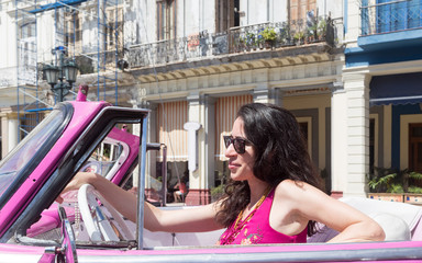 Brunette fashionable girl driving a classical old american car in Cuba