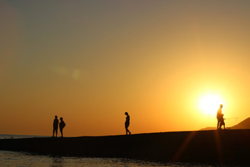silhouette of people in the sun, sunset, silhouettes of people on the pier, evening walk