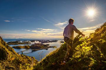 Wall Mural - Hiker going to the top of mount Festvagtinden on Lofoten islands in Norway