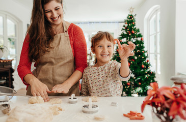 Mother and daughter making cookies for Christmas.