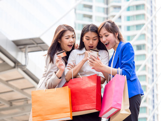 Woman shopping concept, asian woman holding colorful shopping bags and credit cards in shopping mall/city with happy, funny feeling