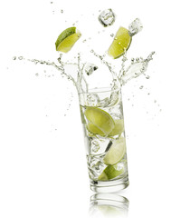 Fototapete - glass full of water with lime slices and ice cubes falling and splashing water, on white background