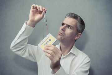Clueless man holding an audio cassette