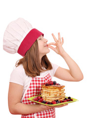 little girl cook with pancakes and ok hand sign