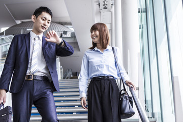 A business couple is descending the stairs while worrying about time