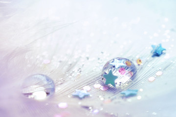 Art abstract background celebratory. Drop water, sequins and stars on feather light blue and silvery colors with soft focus macro. Colorful glamorous template for congratulation, party, Christmas.
