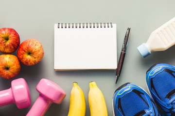 Fitness and healthy active lifestyle background concept. Dumbbell, sneakers,  milk bottle, apples, bananas and blank notebook on clean background. Top view with copy space.