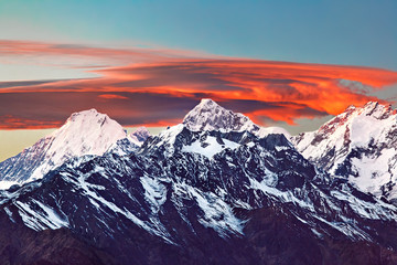 Snowy mountain range with bright orange sunset lenticular clouds