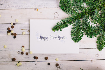 Postcard with congratulations and chocolate ,tree branch on white wooden background. Lettering. Art. Drawing. New year. Studio