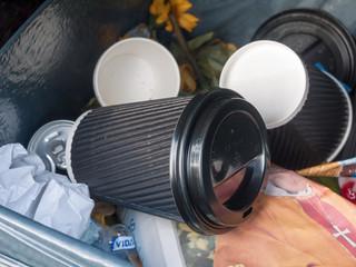 black coffee cup inside bin outside in public