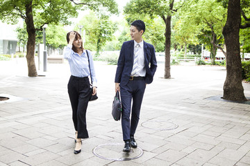 Business couple talking while walking outside