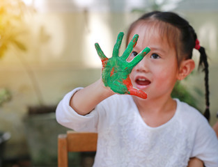 Cute little girl with painted hands with color green-orange in the park, Focus at her hand.