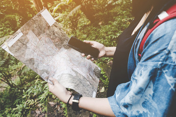 traveler girl using smartphone while looking map in Nature on peak of  mountain.  Thailand. hipster girl compare using map and navigation app on the mobile phone.