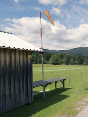 Mountain small airport. Wind sleeve meter. Wooden cottage. Green lawn landing area. Travel destination for holidays. Mountain scenery near Salzburg. Hills in background, grassy pasture in foreground.