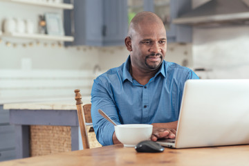 Mature African man using a laptop over breakfast