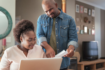 African couple paying bills online together at home
