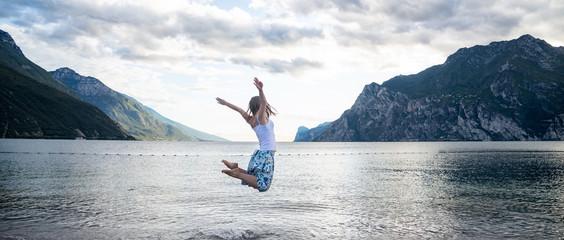 Woman jumping at the lake