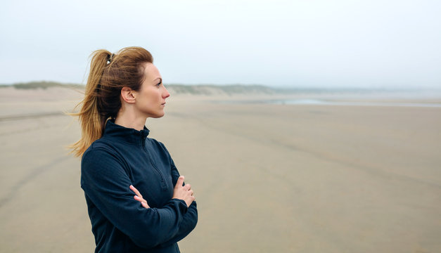 Woman looking at sea on the beach in autumn
