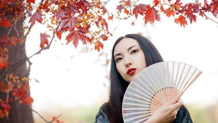 Beautiful young Asian woman with fan on background of red maple