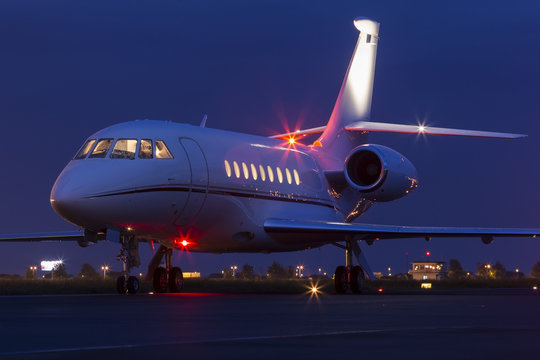 Large modern private business jet ready to take off at night