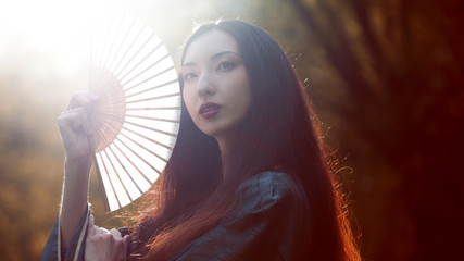 Portrait of young beautiful Asians in grey kimono and with a fan, outdoor