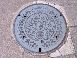 A manhole cover of Osaka city, Kansai region, Japan. Many flowers engraved on manhole cover as a memorial of 100th Anniversary of the city and first year of Heisei period.