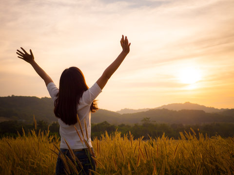 Silhouette woman rising hands and face to sunlight in the morning with freedom, fresh, soft feeling.