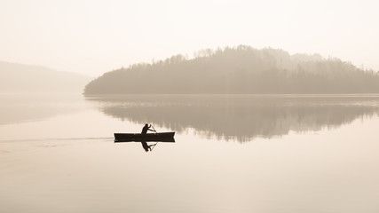 Foggy day.  A man is swimming in a boat.