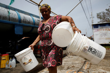 A woman carries buckets to be filled with water from a tank truck at an area hit by Hurricane Maria in Canovanas
