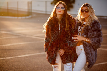two glamorous girlfriends in mink coats and sunglasses walking on the street