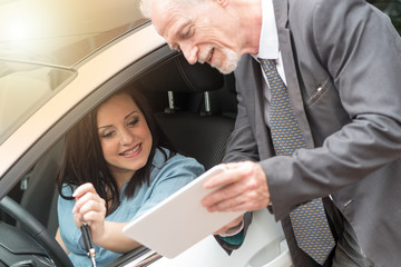 Car salesman giving informations on tablet to young woman, light effect