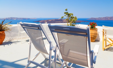 Lounge chairs on beautiful white flowered terrace with sea view in Santorini, Greece