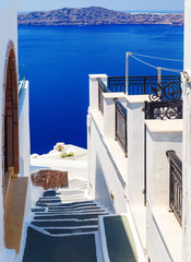 White architecture with steps leading down to the sea on Santorini island, Greece. Beautiful landscape with sea view.