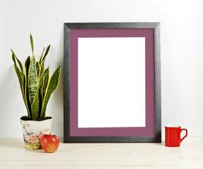 Mock up of blank photo frame with plant pot, mug and apple on wooden shelf.