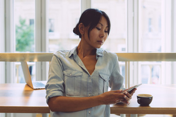 Attractive asian woman wearing casual clothes is typing messages on her mobile phone while standing beside the wooden table with a portable computer on it in a modern coffee shop with big windows.