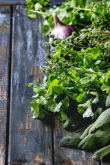 Variety of fresh organic herbs coriander, sage, oregano with garlic over old wooden plank background. Close up with space.