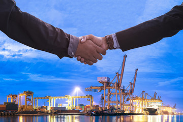 Business Collaboration, Businessman shake hands with transportation logistic import export background night city town.