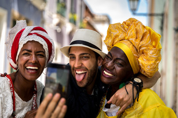 "Tourist taking selfie photos with local ""Baianas"" in Salvador, Bahia, Brazil"