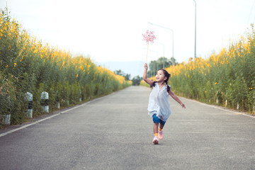 Cute asian little child girl playing with wind turbine and running on the road in the garden in vintage color tone