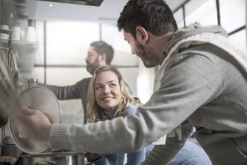 Couple preparing food in kitchen with man in the background